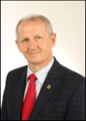 Uśmiechnięty około 55 letni mężczyzna o siwych włosach ubrany w białą koszulę, czerwony krawat i czarną marynarkę z motywem kraty.